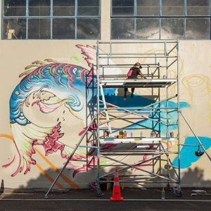 Lauren painting a mural in New Zealand. Image courtesy Lauren YS.