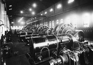 An interior view of the Denver Tramway Company power plant (now REI) at 14th and Platte. A line of large turbines fill the room and one wall is lined with electric switches. Image courtesy Stephen H. Hart Library & Research Center, History Colorado.