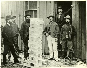 "a group of men standing around a stack of silver bullion bars (ingots) at the Argo Smelting Company in Black Hawk, Colo., photographed by an unidentified photographer circa 1873. A caption in the album indicates that this was the first silver made by Richard Pearce (b. 1838; Manager at Argo) and that Pearce ""brought these men to Colorado with him from Swansea, Wales."" Men are identified as Richard Pearce (on left), Josiah Burgess (refiner; on right), Thomas Thomas (mason; in light overalls), and William Abbe (foreman; in doorway)."