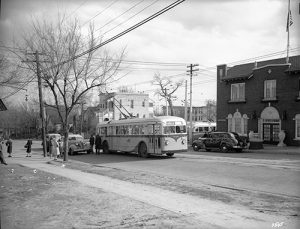 Passengers stand around a J.G. Brill trolley coach (electric bus) at the corner of 16th and Boulder Streets. The Olinger Mortuary can be seen nearby. Image courtesy Stephen H. Hart Library & Research Center, History Colorado.
